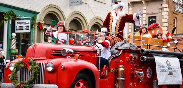 Santa riding in an old fire truck in a parade